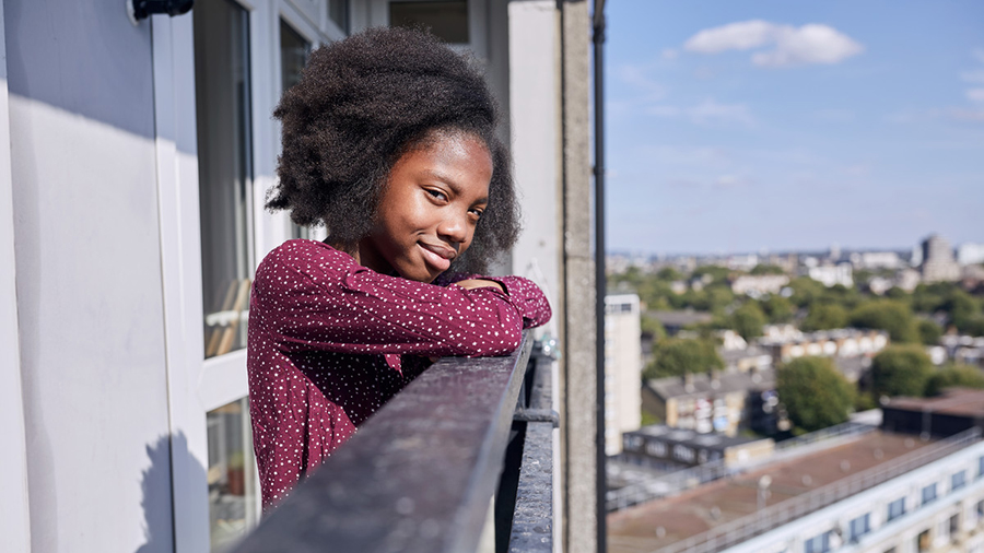 Young girl standing on a balcony, smiling