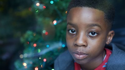 Young boy sitting in front of Christmas tree