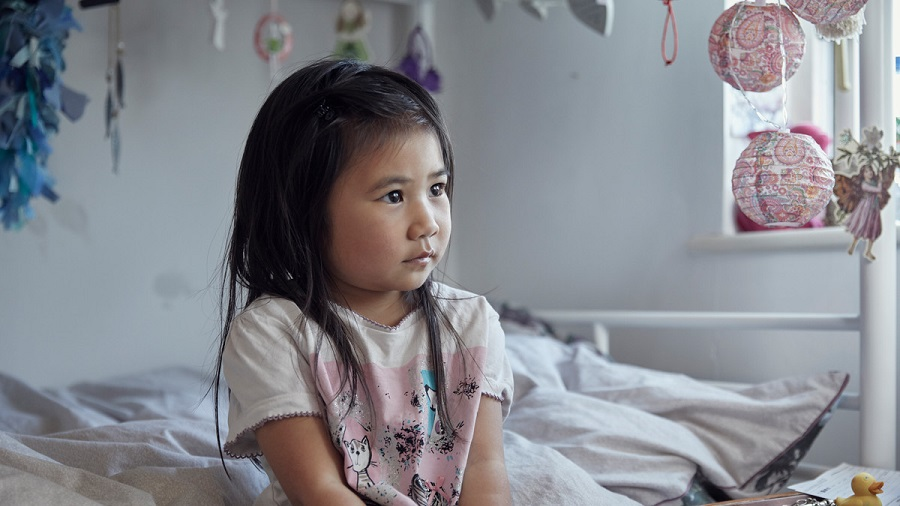 Young female child sat in her bedroom