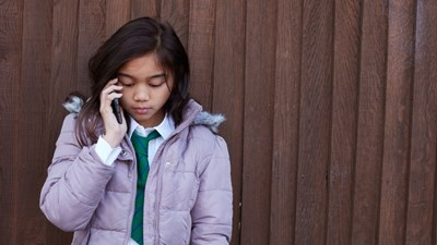 Teenage girl in the street speaking on a mobile phone