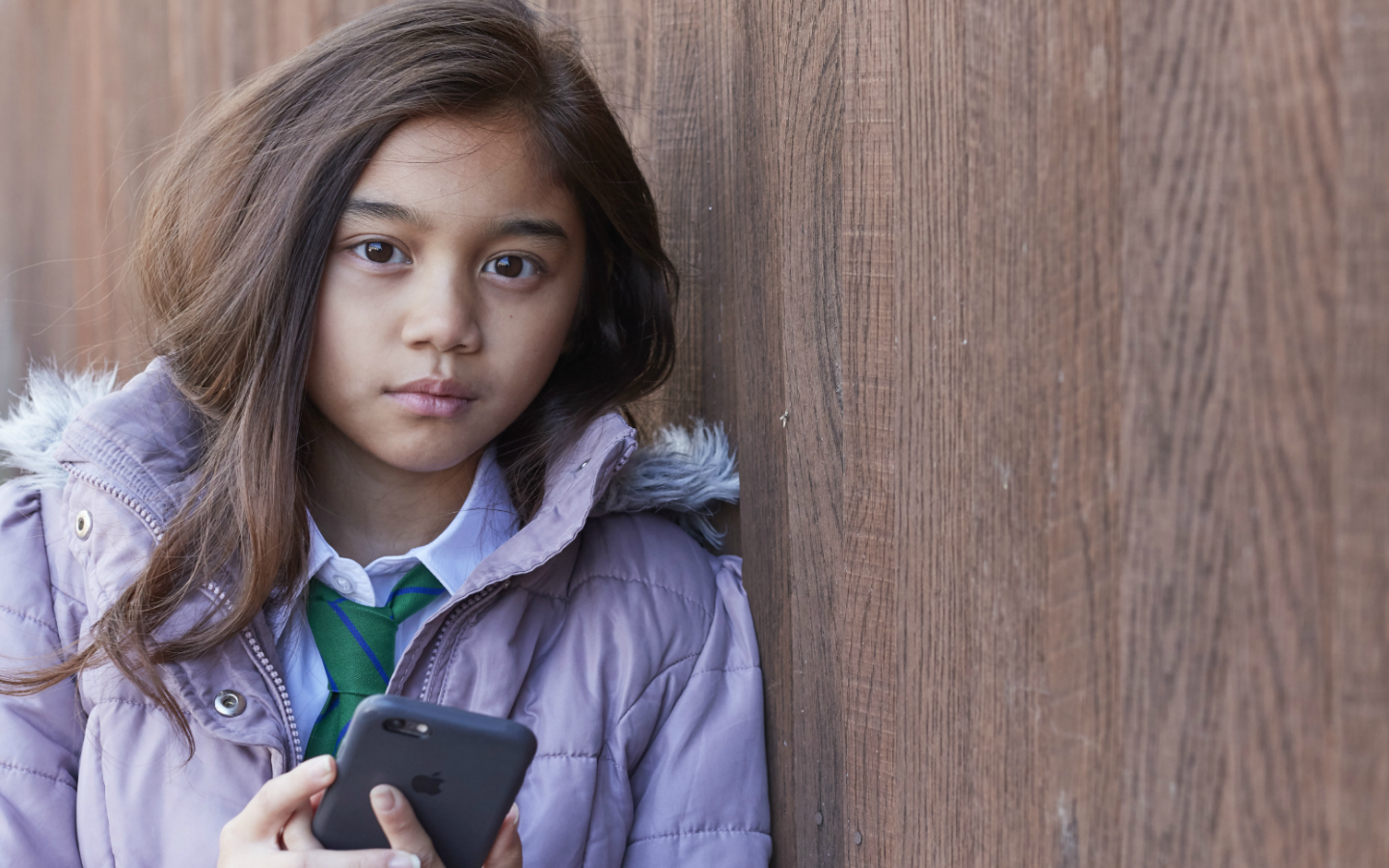 Young girl standing outside holding phone