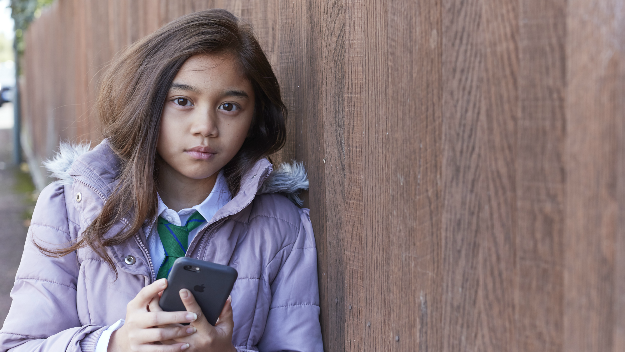 Young girl leaning against fence, holding phone