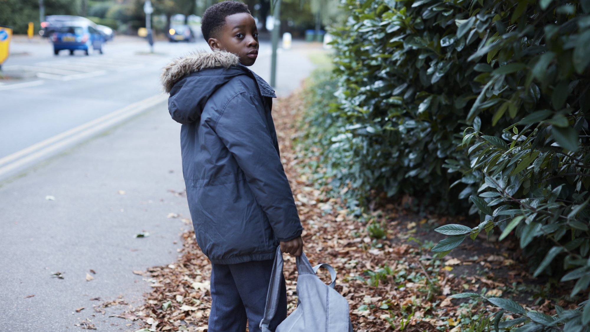 Young boy standing outside in street wearing coat