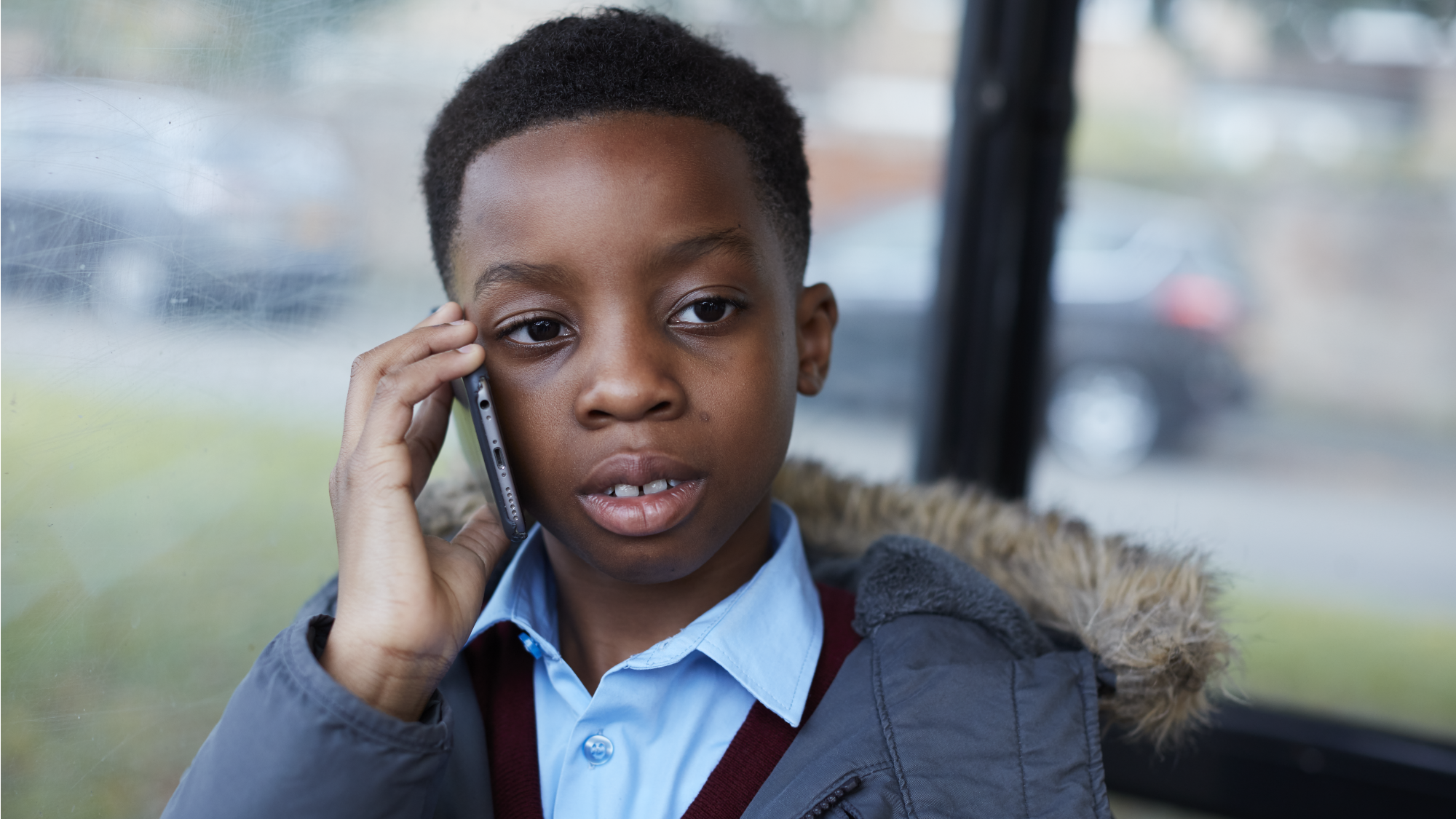 Young boy on phone sitting in bus stop