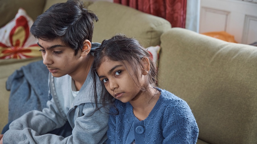 Young boy and girl sat on sofa