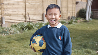 Boy holding a football in back garden
