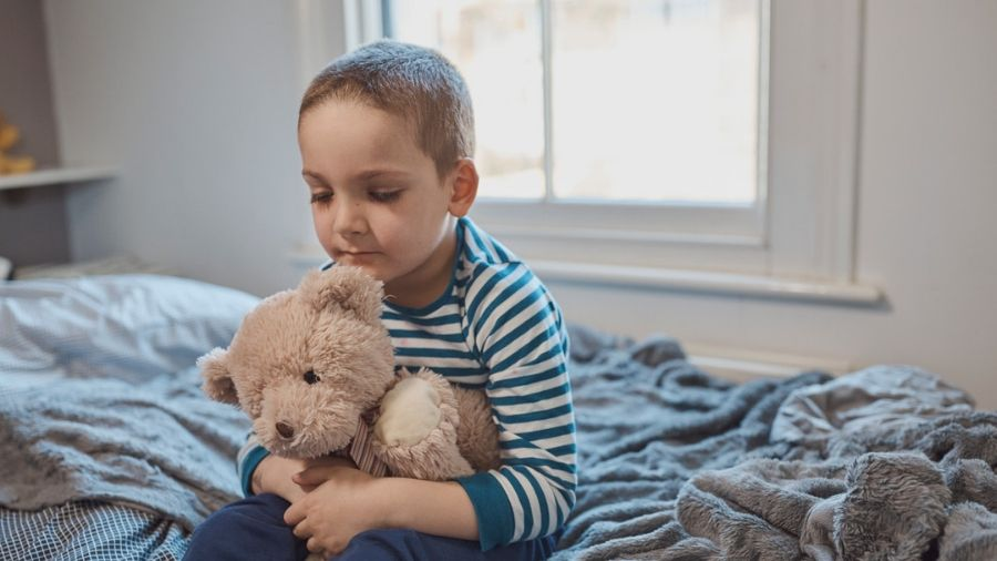 Young boy with teddy bear, sitting on bed