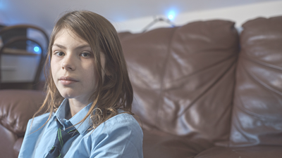 Young girl sitting indoors, looking directly at camera