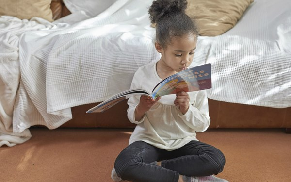 a girl sits on the floor reading a picture book