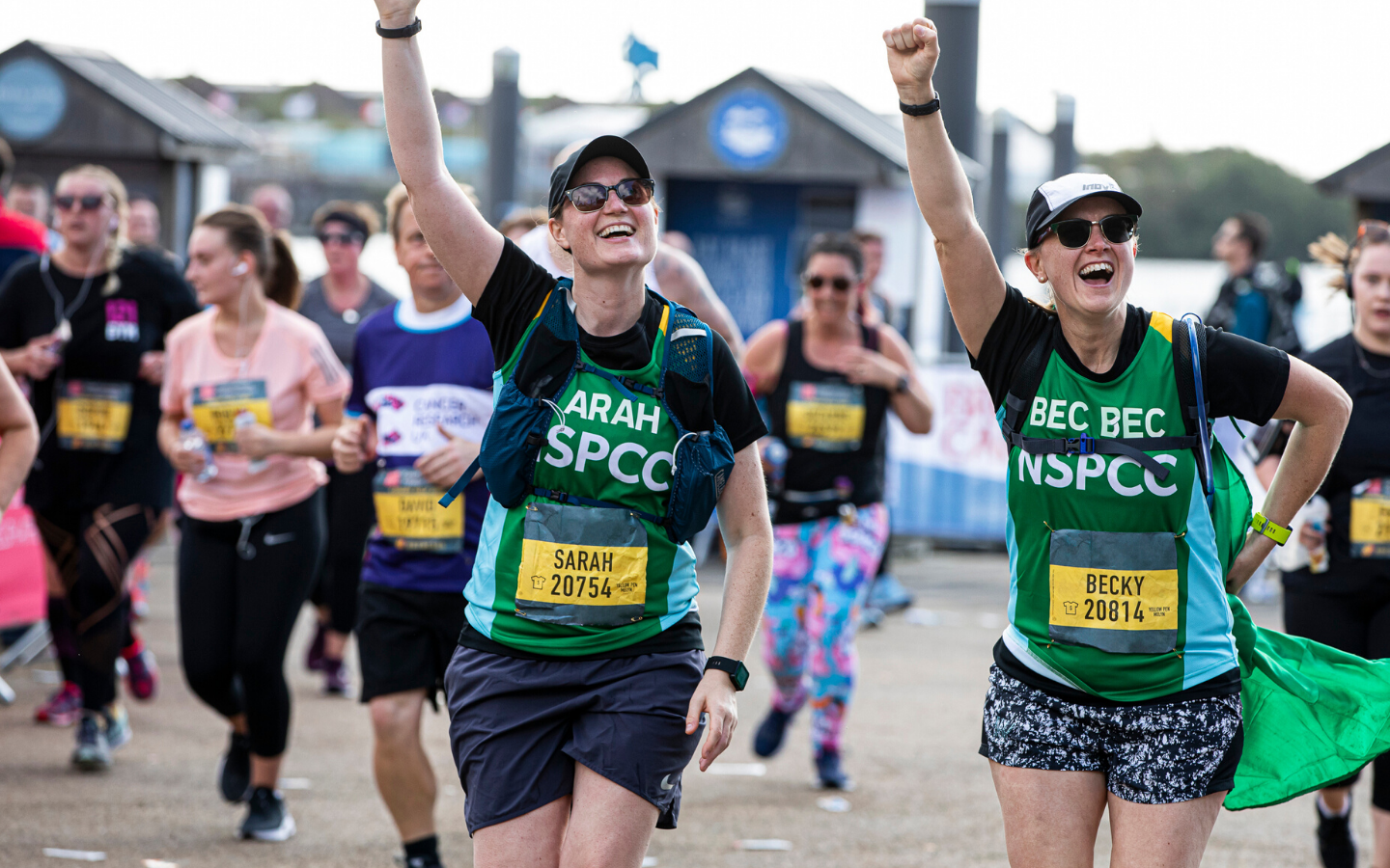 Two women in NSPCC vests reach the finish line cheering and smiling.