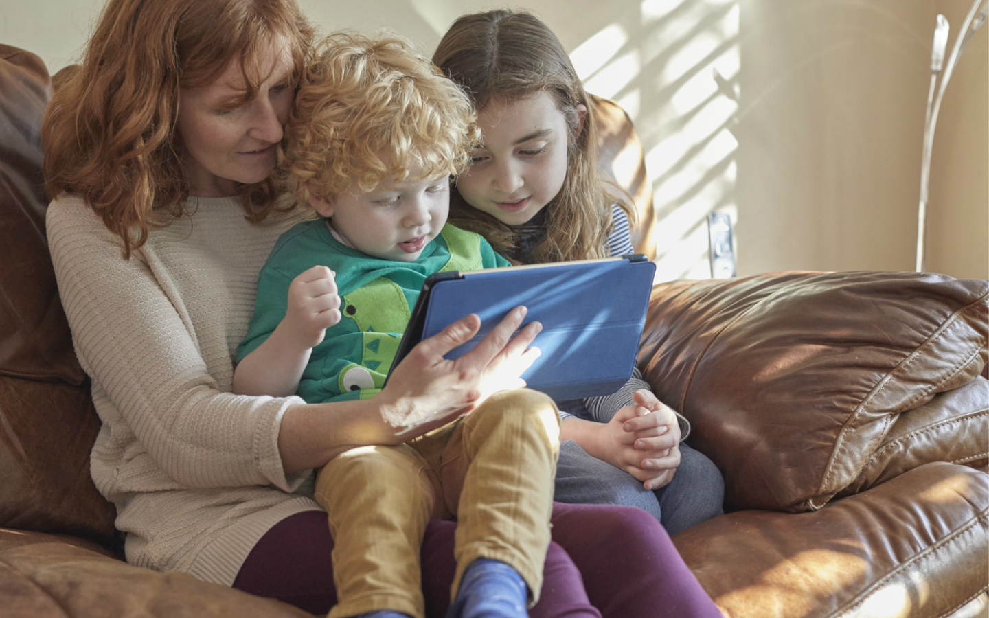 Mother and small children looking at tablet together