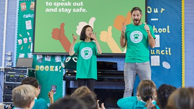 2 volunteers delivering a Speak Out Stay Safe assembly to a group of primary school children.