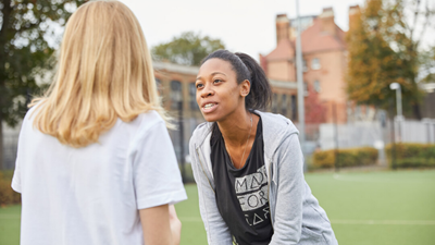 Sports teacher talking to young girl on a football pitch