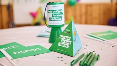 NSPCC fundraising materials and a money box on a table
