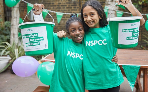 Two young girls holding fundraising buckets for the NSPCC