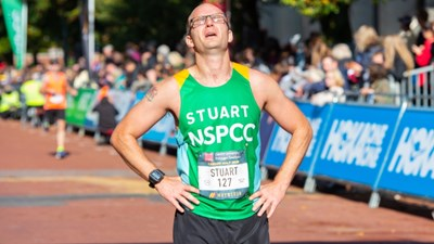 A man stops to catch his breath at the finish line of a half marathon