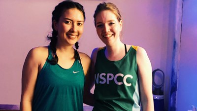 Two women wearing NSPCC vests at a yoga class