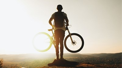A silhouette of a man at the top of a valley holding an adventure bike