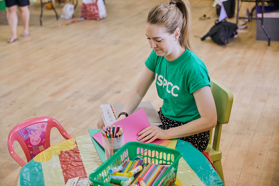 Young woman sat down preparing children's activities for an event